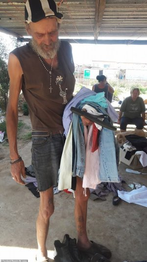 A frail-looking bearded man holds a pile of his clothes and a pair of flip flops at the camp which he calls home