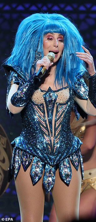Elaborate: Cher donned a loud - and large - blue wig as she belted out her latest hits clutching hold of a golden microphone
