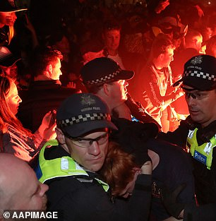 Police move in as flares are set off on Swan Street as Tigers fans celebrate their team's victory in the 2019 AFL Grand Final