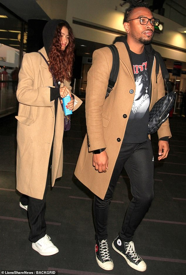 Twinsies:The actress and singer was traveling with her brother Austin, and thesiblings were dressed almost identically in long trench coats, black hoodies and black pants