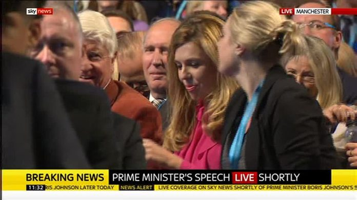 The defiant speech by Mr Johnson was watched from the audience by girlfriend Carrie Symonds (pictured centre)