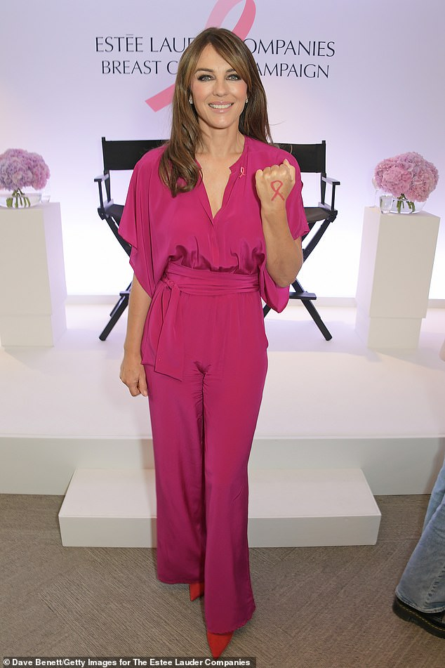 Lovely: The actress looked sensational in the one-piece with matching heels, as she proudly sported the breast cancer logo on her right hand