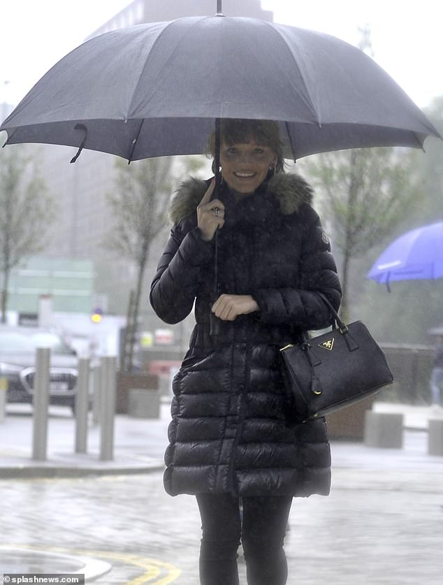Wrapped up! Bake Off judge Paul Hollywood's ex wrapped up warm in a padded coat boasting a furry collar, while shielding herself from a downpour with a large black umbrella