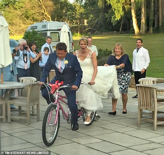 In a shot from his wedding day in May, he and his second wife Emily are seen riding a pink tandem
