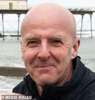 Police searching for missing photographer Keith Morris, 61, (pictured) have found a body in the water at a beach near Aberystwyth