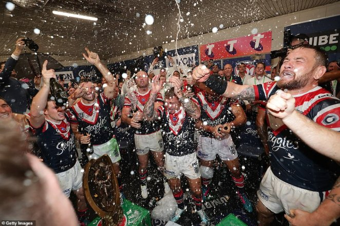 Roosters players celebrate victory by spraying champagne in the changing rooms