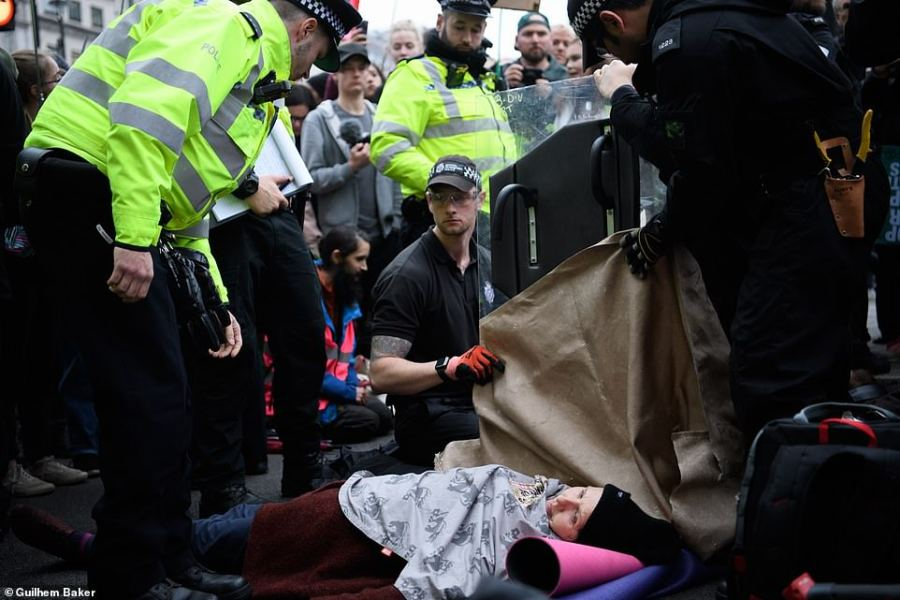 Police officers in Trafalgar Square use angle grinders and de-bonder to release to Extinction Rebellion (XR) activists who locked and glued themselves together