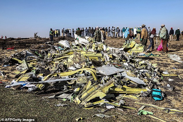 People stand near collected debris at the crash site of Ethiopia Airlines near Bishoftu, a town some 60 kilometres southeast of Addis Ababa, Ethiopia, a day after the aircraft came down