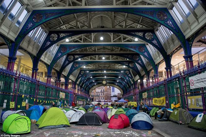 Dozens of protestors from 'Animal Rebellion', an extreme vegan branch of Extinction Rebellion, camped out overnight waiting for traders to arrive for work in the early hours - only to stop them setting up their stalls and covering them with fruit and veg