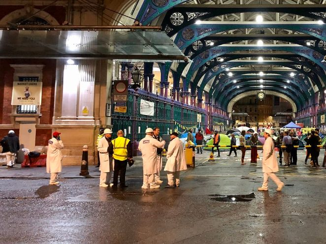 Extinction Rebellion vegans have sparked fury by forcing out meat traders (pictured in white) from London's famous Smithfield Market, setting up tents overnight and covering their stalls with fruit and veg