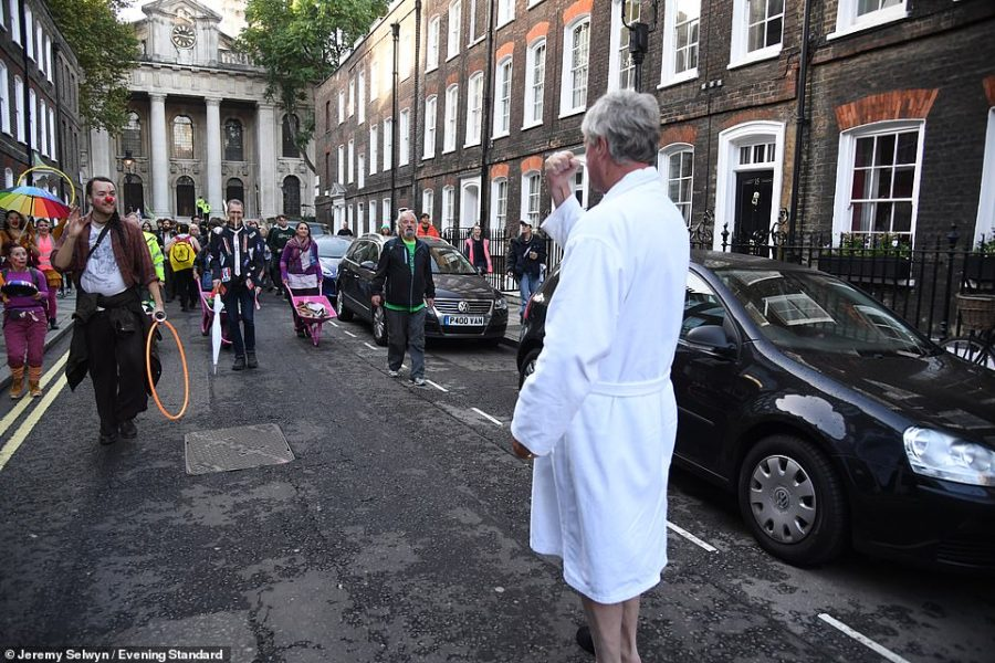 Former Tory party treasurer Lord Andrew Fraser confronts protesters in Westminster and shakes his fist at them while wearing his dressing gown this morning