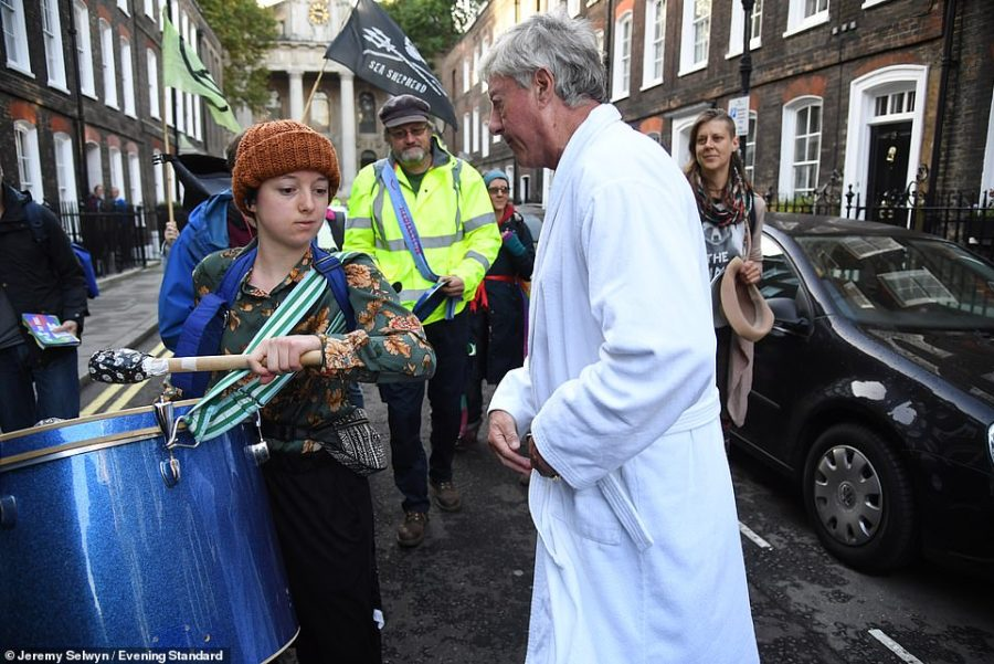 Fuming: Lord Fraser is pictured trying to reason with a group of protestors in his bath robe