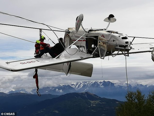 Rescuers spend an hour-and-a-half trying to free the 62-year-old pilot and his passenger, 55, from the tangled plane high above the Italian alps