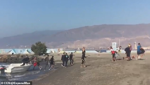 The footage shows them cheering and reportedly shouting 'we are in Spain' as they reach land