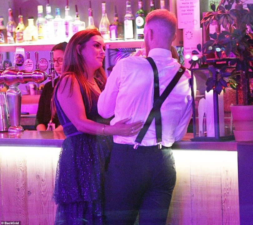 Clare Stokes places an arm on her husband's lower back as they drink and celebrate his successful sporting year