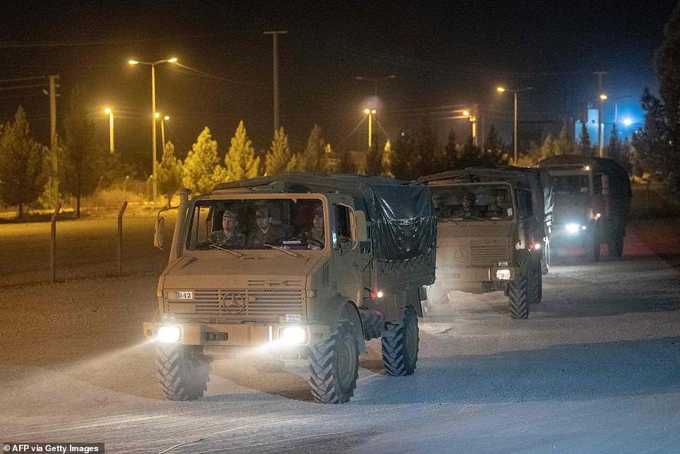 Turkish army soldiers drive towards the border with Syria near Akcakale in Sanliurfa province overnight Tuesday