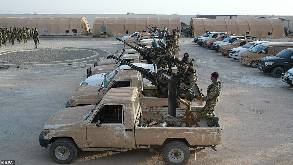 Turkey-backed members of Syrian National Army riding in machine gun-mounted trucks yesterday as troops amassed along the Turkish-Syria border