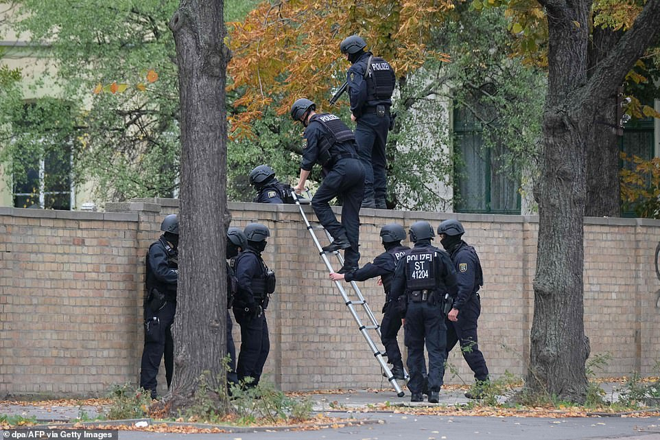 Policemen climb over a wall close to the site of a shooting in Halle an der Saale, eastern Germany