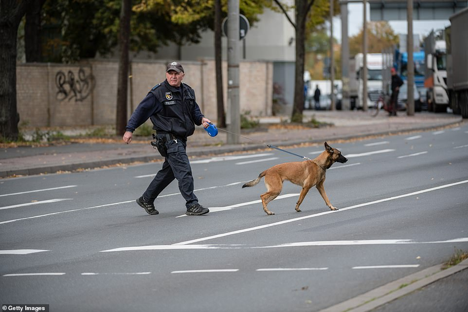 An officer leads a bomb-sniffing dog across the street in Halle, following reports that grenades were thrown by a gunman who targeted a synagogue in the city