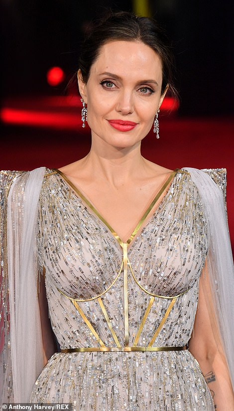 Statement: Angelina's gold body jewellery put emphasis on her slender waist while the striking back design showed off her tattoos