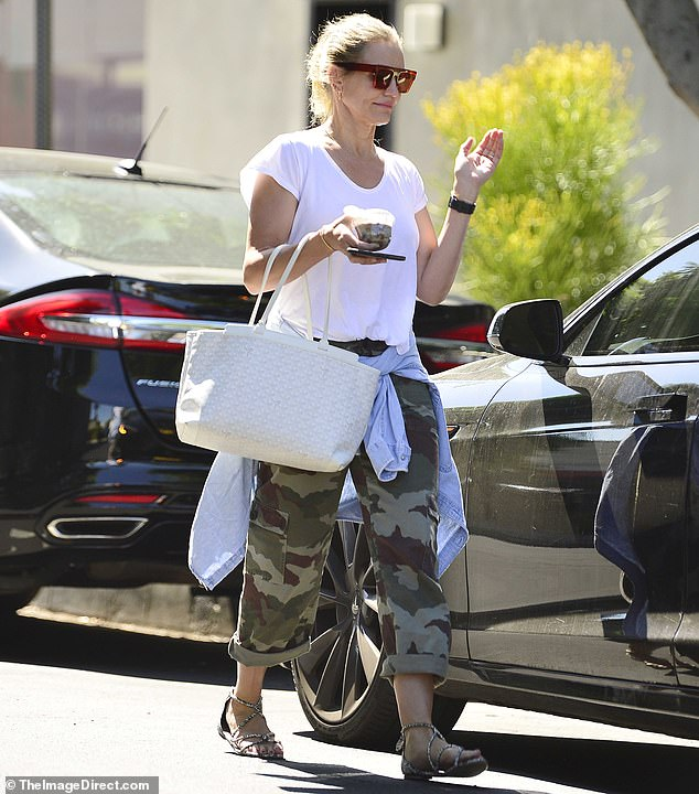 On the move:The 47-year-old teamed a simple white T-shirt with a pair of camouflage trousers, jazzing up the look with a chic white Goyard handbag