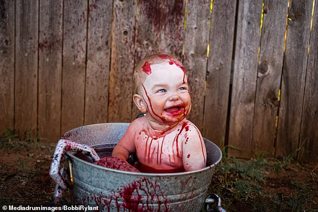Gruesome photos of 10-month-old Kamden show the baby sitting in a bucket of 'blood', gnawing on a brain in a horror-inspired photo shoot in the family's back garden Oklahoma