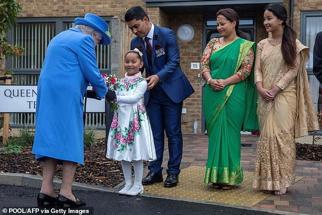During her visit to the housing development the Queen met with a local veteran and his young family, with one little girl presenting the royal with flowers