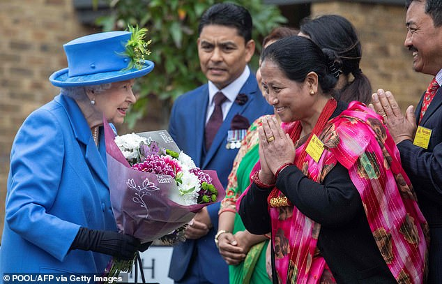 Queen Elizabeth II was presented with flowers while she met with local families at the development in Morden
