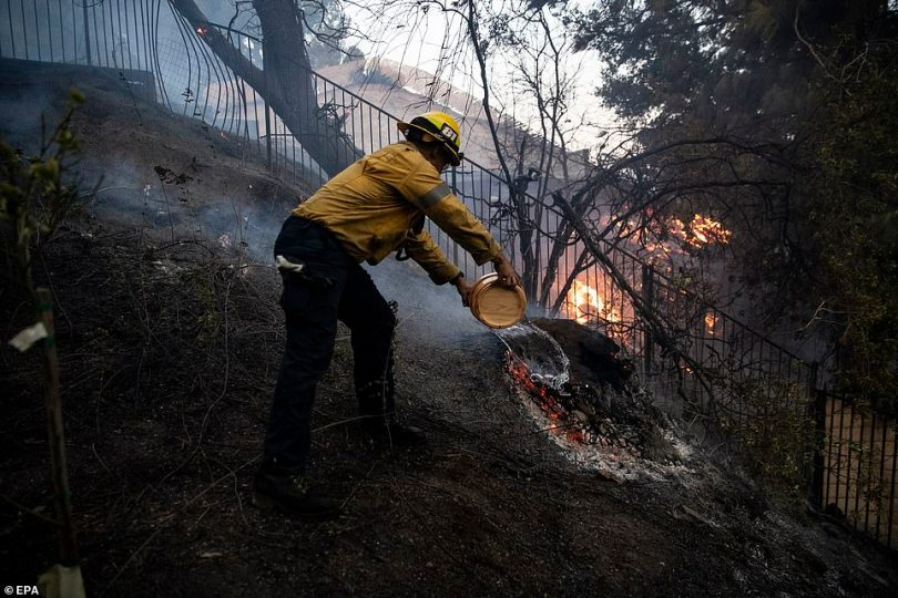 A firefighter works to extinguish the Saddleridge Fire in Porter Ranch early Friday morning with a bucket of water