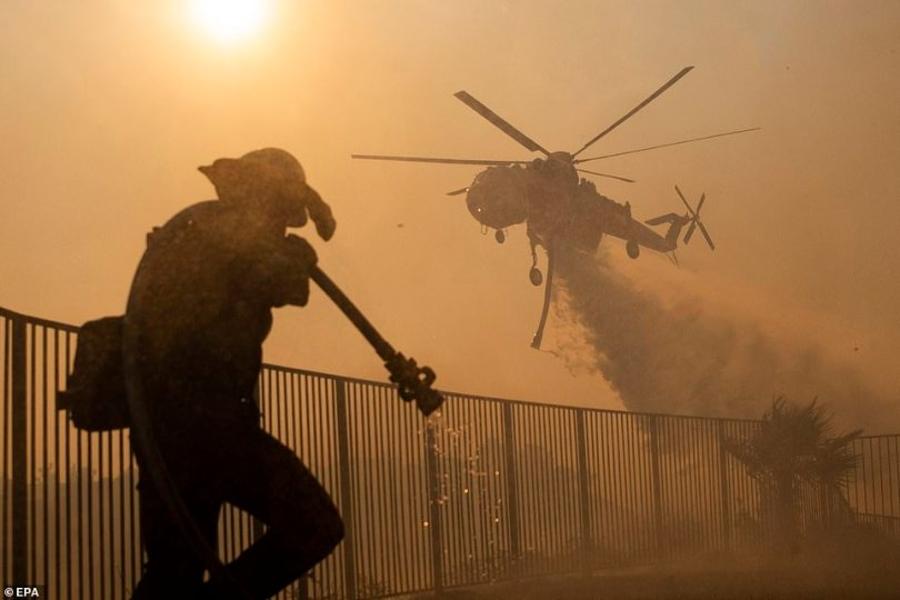 Terrifying footage shows crews battling a California wildfire fueled by winds as homes burned and thousands of people were forced to evacuate. Pictured: Firefighters work to extinguish the Saddleridge Fire in Porter Ranch on Friday