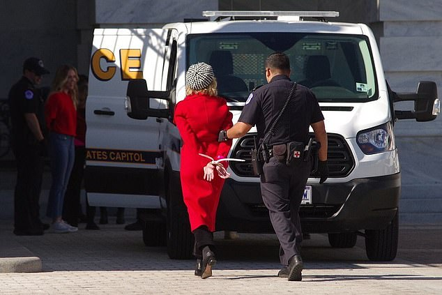 Fonda walked away hands behind her back as she was taken to a police car
