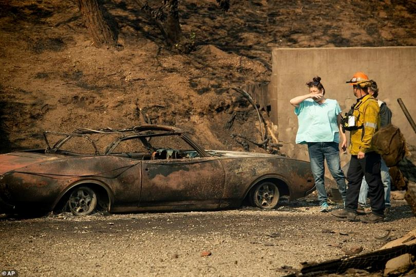 The wildfire broke out after 9pm on Thursday in Sylmar, north of Los Angeles, along the 210 Freeway. Pictured:A couple walk with a firefighter to survey the scorched remains of their home and vehicle
