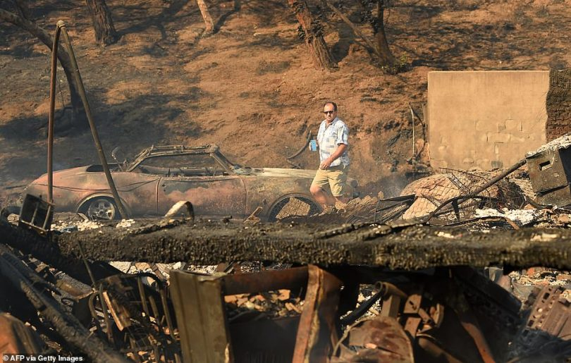 Officials ordered more than 100,000 people to evacuate as the wildfire, fueled by winds, destroyed at least 25 homes in the Granada Hills, Porter Ranch and Oakridge Estates neighborhoods. Pictured:Eyad Jarjour (pictured) views his neighbor's burned residence after flames from the Saddleridge Fire tore through the region in Granada Hills