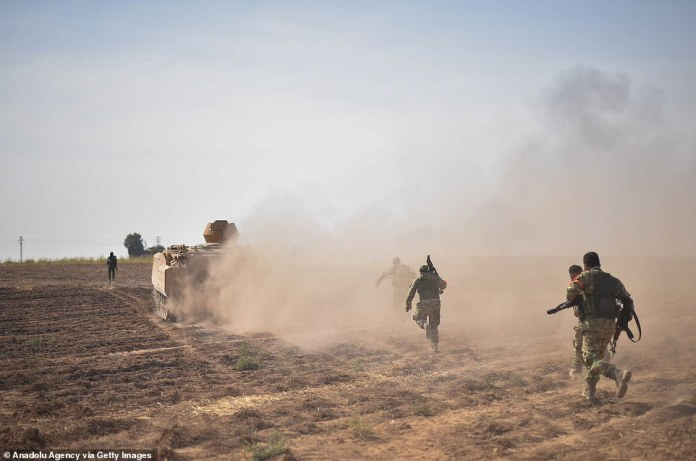 Members of the Syrian-backed Syrian Free Army enter the city of Rasulayn, Syria, to clear the city on Friday. Turkey is progressing progressively in the northern part of Kurdish-controlled Syria where it says it wants to create a