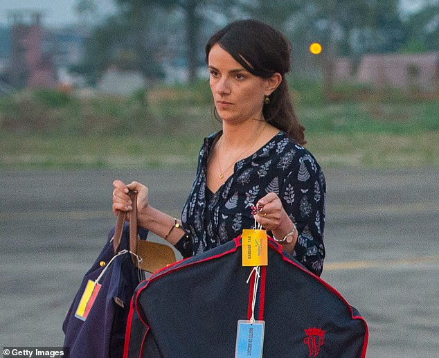 In 2016, she was spotted lugging William's red-and-blue suit cover bearing his cipher, as well as a large Longchamp pliage bag
