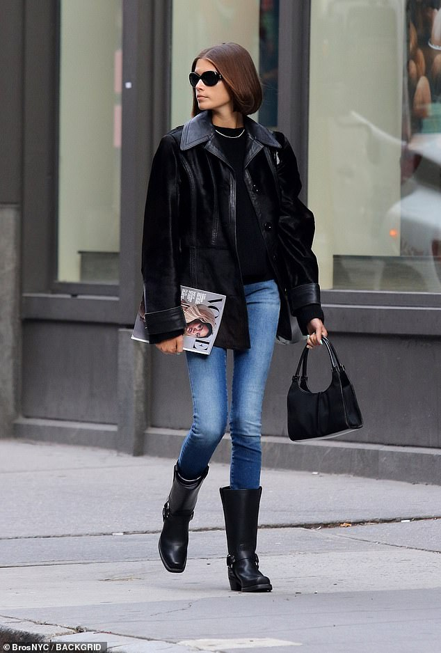 Casual Friday: Cindy layered a black shirt with a suede and leather cover up with cuffed sleeves; she carried a small black handbag