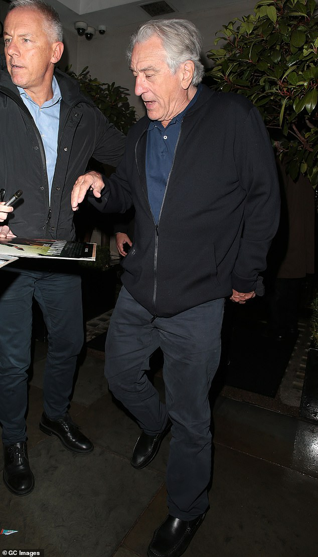 Relaxed and put together: De Niro cut a casual figure in black chinos, a navy polo shirt and simple loafers