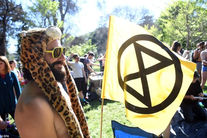 Brave semi-naked activists waved the Extinction Rebellion flag, representing the organisation, while others had the symbol painted on their bodies