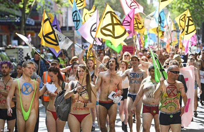 Hundreds of protesters waved the Extinction Rebellion flag throughout the march while others had the symbol painted on their bodies