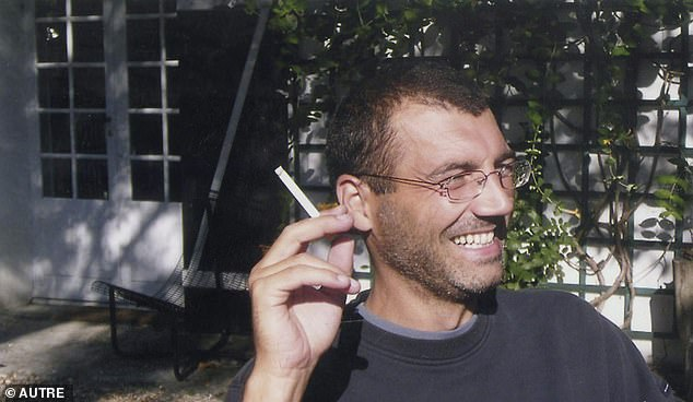 Xavier Dupont de Ligonnes smiling, a cigarette in his hand, in the garden of his house in Nantes in August 2003