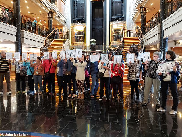 Tensions boiled over in the ship's atrium, with mobile phone footage showing passengers confronting staff and later holding up signs demanding refunds (pictured)
