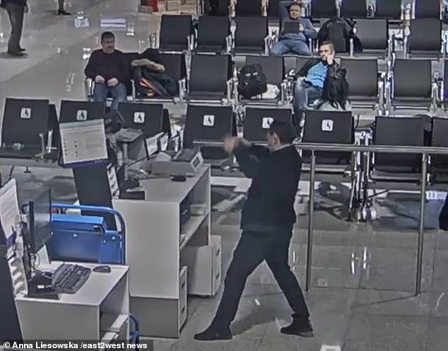 After some unsuccessful attempts, the tourist moves away from the door and instead chooses to tear down the panels and barriers placed around the check-in counter.