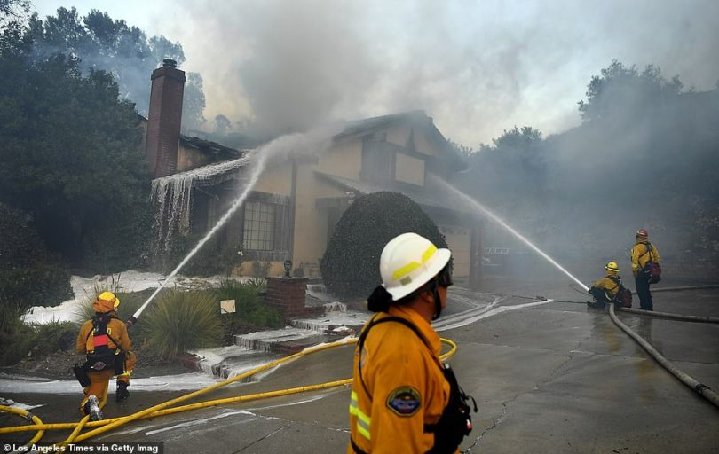 Orange County firefighters work knock down a house fire on Singing Hills Drive as the Saddleridge Fire burns in Porter Ranch