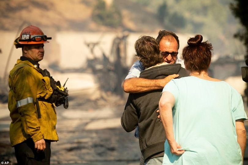 A man comforts his neighbor after the Granda Hills resident's home burned to the ground as a result of the fire