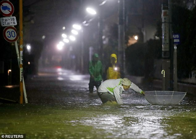 Pedestrians were seen wading through flooded roads as the powerful storm took hold in Japan