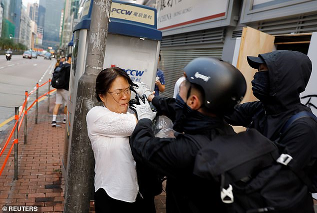 A woman scuffles with anti-government demonstrators during a protest against the invocation of the emergency laws in Hong Kong