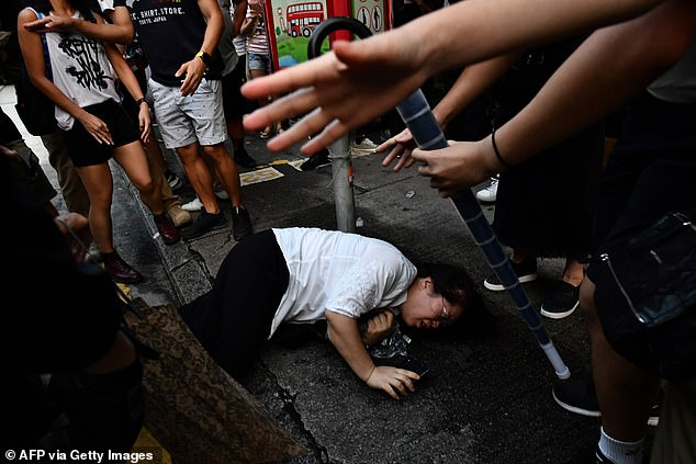 A woman lies on the ground after she scuffled with protesters when she tried to remove a facemask worn by one of them