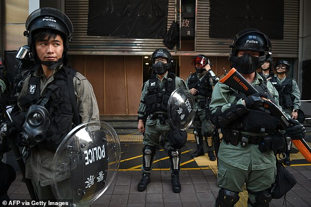 Hong Kong riot police stand guard as protests take place again across the region