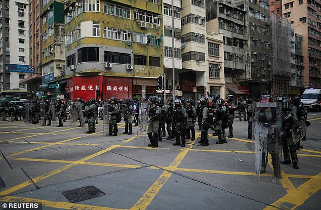 Police officers block the street during a protest against the invocation of the emergency laws in Hong Kong