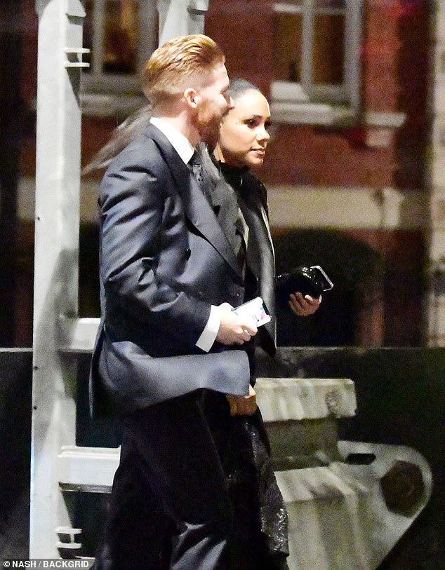 Sharp: Neil looked smart in a suit and crisp shirt on Thursday and held his phone as he walked